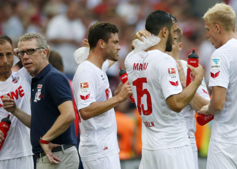 Cologne's Austrian head coach Peter Stoeger (2nd L) and Cologne's players refresh during a break interrupting the match due to heat during the German first division Bundesliga football match of FC Cologne vs SV Darmstadt 98 in Cologne, western Germany, on August 27, 2016. / AFP / NORBERT SCHMIDT / RESTRICTIONS: DURING MATCH TIME: DFL RULES TO LIMIT THE ONLINE USAGE TO 15 PICTURES PER MATCH AND FORBID IMAGE SEQUENCES TO SIMULATE VIDEO. == RESTRICTED TO EDITORIAL USE == FOR FURTHER QUERIES PLEASE CONTACT DFL DIRECTLY AT + 49 69 650050 (Photo credit should read NORBERT SCHMIDT/AFP/Getty Images)