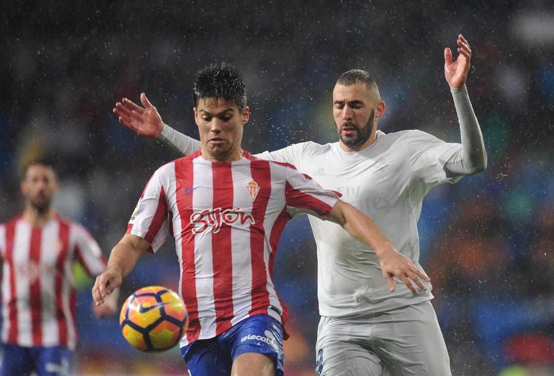 MADRID, SPAIN - NOVEMBER 26: Karim Benzema of Real Madrid CF is beaten to the ball by Jorge Mere of Real Sporting de Gijon during the La Liga match between Real Madrid CF and Real Sporting de Gijon at Estadio Santiago Bernabeu on November 26, 2016 in Madrid, Spain.
