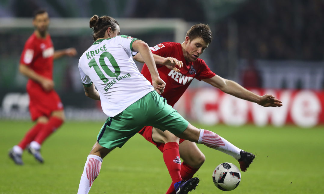 BREMEN, GERMANY - DECEMBER 17: Max Kruse (L) of Bremen and Dominique Heintz (R) of Koeln compete for the ball during the Bundesliga match between Werder Bremen and 1. FC Koeln at Weserstadion on December 17, 2016 in Bremen, Germany.