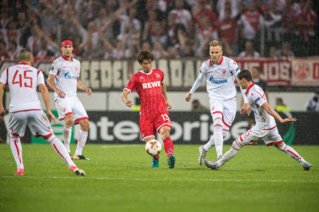 COLOGNE, GERMANY - SEPTEMBER 28: Yuya Osako of Koeln acts against the defense of Belgrade during the UEFA Europa League group H match between 1. FC Koeln and Crvena Zvezda at RheinEnergieStadion on September 28, 2017 in Cologne, Germany.