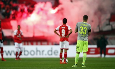 MAINZ, GERMANY - NOVEMBER 18: Yoshinori Muto #9 of Mainz and Matthias Lehmann of Koeln react as fans of Koeln burn flares during the Bundesliga match between 1. FSV Mainz 05 and 1. FC Koeln at Opel Arena on November 18, 2017 in Mainz, Germany. (Photo by Alex Grimm/Bongarts/Getty Images)