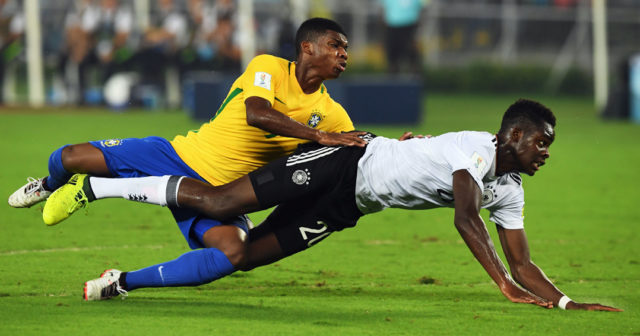 Yann Bisseck of Germany and Lincoln (L) of Brazil compete for the ball during the quarterfinal football match of the FIFA U-17 World Cup at the Vivekananda Yuba Bharati Krirangan stadium in Kolkata on October 22, 2017. The FIFA U-17 Football World Cup is taking place in India from October 6 to 28. / AFP PHOTO / Dibyangshu SARKAR (Photo credit should read DIBYANGSHU SARKAR/AFP/Getty Images)