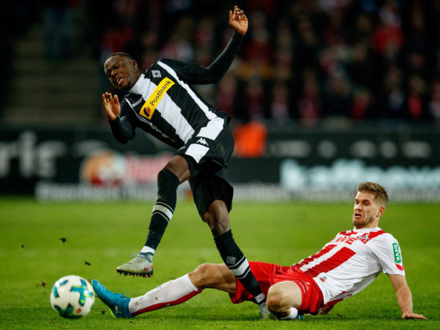 COLOGNE, GERMANY - JANUARY 14: Denis Zakaria of Moenchegladbach is challenged by Simon Terodde of Koeln during the Bundesliga match between 1. FC Koeln and Borussia Moenchengladbach at RheinEnergieStadion on January 14, 2018 in Cologne, Germany.