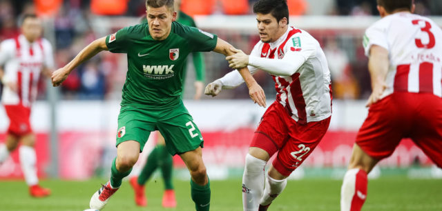 COLOGNE, GERMANY - JANUARY 27: Jorge Mere Perez #22 of 1.FC Koeln and Alfred Finnbogason #27 of Augsburg battle for the ball during the Bundesliga match between 1. FC Koeln and FC Augsburg at RheinEnergieStadion on January 27, 2018 in Cologne, Germany. (Photo by Maja Hitij/Bongarts/Getty Images)