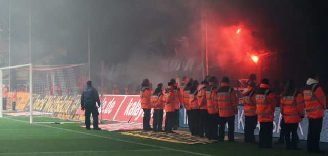 COLOGNE, GERMANY - MAY 05: Security take control of the pitch and stop the fans invading during the final minutes of the Bundesliga match between 1. FC Koeln and FC Bayern Muenchen at RheinEnergieStadion on May 5, 2012 in Cologne, Germany. Fans released smoke bombs and flares. (Photo by Dean Mouhtaropoulos/Bongarts/Getty Images)