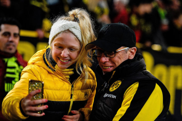 Dortmund's head coach Peter Stoeger (R) poses for a selfie photo with a fan prior to the German first division Bundesliga football match BVB Borussia Dortmund vs VfL Wolfsburg, in Dortmund, western Germany, on January 14, 2018.