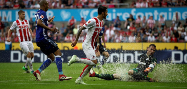 COLOGNE, GERMANY - APRIL 22: Ralf faehrmann (R), goalkeeper of Schalke slides into a water puddle during the Bundesliga match between 1. FC Koeln and FC Schalke 04 at RheinEnergieStadion on April 22, 2018 in Cologne, Germany. (Photo by Maja Hitij/Bongarts/Getty Images)