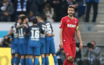 SINSHEIM, GERMANY - MARCH 31: The team of Hoffenheim celebrates the seceding goal and Jonas Hector of Koeln looks dejected during the Bundesliga match between TSG 1899 Hoffenheim and 1. FC Koeln at Wirsol Rhein-Neckar-Arena on March 31, 2018 in Sinsheim, Germany.