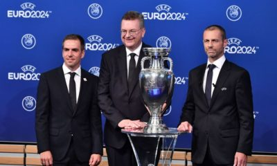 (FromL) Head of Germany's bid to host the Euro 2024 Philipp Lahm, German Football Association (DFB) president Reinhard Grindel and UEFA president Aleksander Ceferin pose with the UEFA Euro trophy after it was announced that Germany was elected to host the Euro 2024 fooball tournament during a ceremony at the headquarters of the European football's governing body in Nyon on September 27, 2018. - UEFA selected the host of the 2024 European Championship today in a vote pitting a safe German bid against a riskier Turkish proposal that offers a chance to explore new terrain. (Photo by Fabrice COFFRINI / AFP) (Photo credit should read FABRICE COFFRINI/AFP/Getty Images)