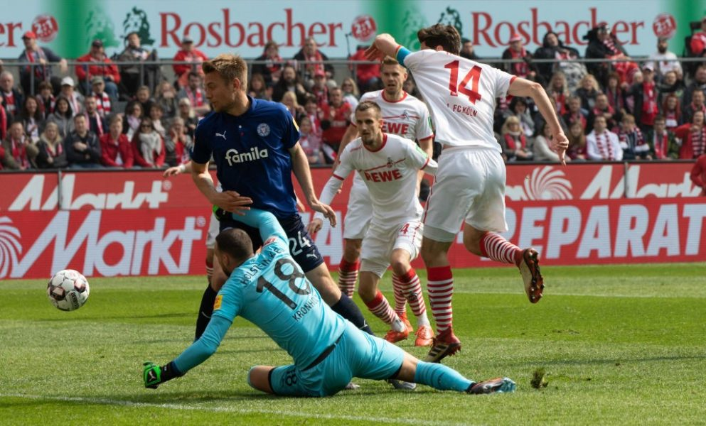COLOGNE, GERMANY - MARCH 31: Jonas Hector of Cologne (R) and goalkeeper Kenneth Kronholm of Kiel battle for the ball during the Second Bundesliga match between 1. FC Koeln and Holstein Kiel at RheinEnergieStadion on March 31, 2019 in Cologne, Germany. (Photo by Juergen Schwarz/Bongarts/Getty Images)