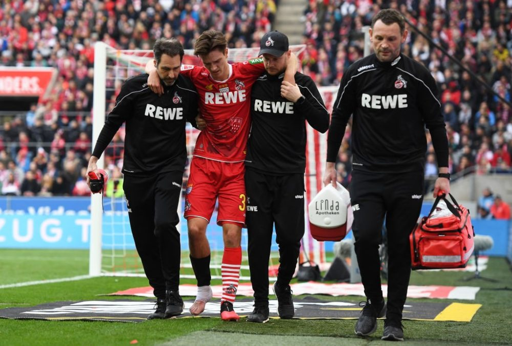 COLOGNE, GERMANY - FEBRUARY 16: Noah Katterbach of FC Koln receives medical attention during the Bundesliga match between 1. FC Koeln and FC Bayern Muenchen at RheinEnergieStadion on February 16, 2020 in Cologne, Germany. (Photo by Jörg Schüler/Bongarts/Getty Images)