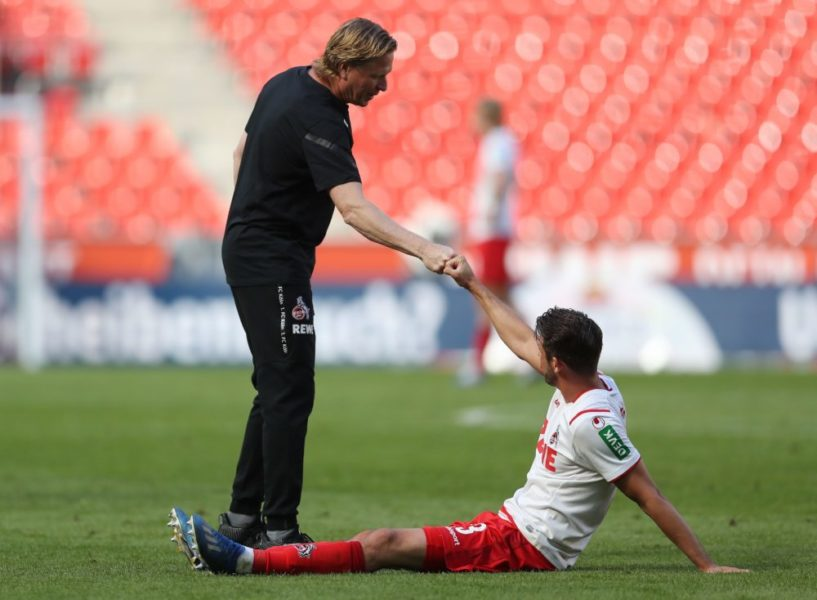 Cologne's German coach Markus Gisdol (L) and Cologne's German forward Mark Uth do a fist bump after the German first division Bundesliga football match FC Cologne v Mainz 05 on May 17, 2020 in Cologne, western Germany as the season resumed following a two-month absence due to the novel coronavirus COVID-19 pandemic. (Photo by Lars Baron / POOL / AFP) / DFL REGULATIONS PROHIBIT ANY USE OF PHOTOGRAPHS AS IMAGE SEQUENCES AND/OR QUASI-VIDEO (Photo by LARS BARON/POOL/AFP via Getty Images)