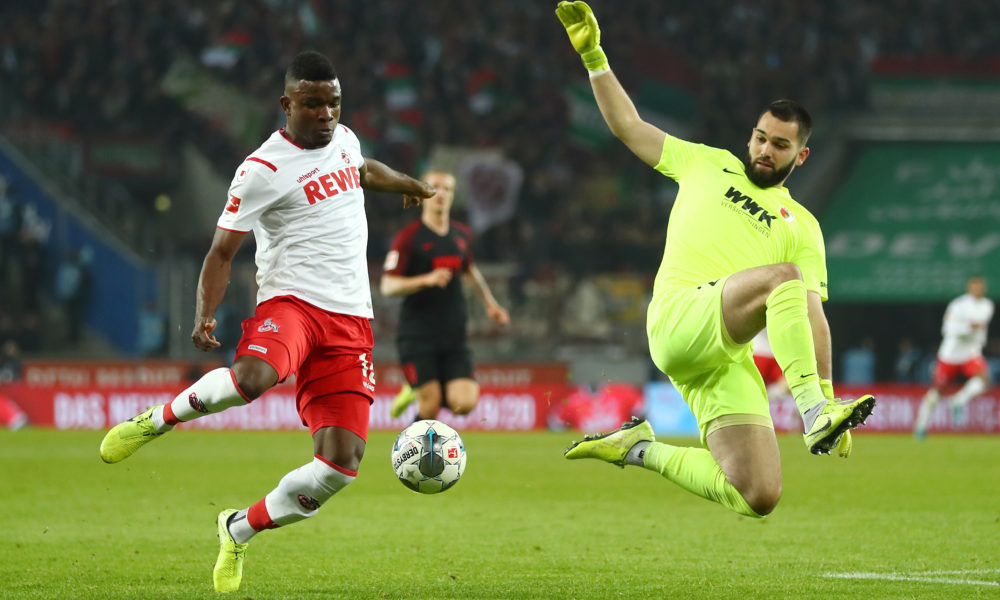 COLOGNE, GERMANY - NOVEMBER 30: Jhon Cordoba of 1. FC Koeln runs with the ball past Tomas Koubek of FC Augsburg before scoring his team's first goal during the Bundesliga match between 1. FC Koeln and FC Augsburg at RheinEnergieStadion on November 30, 2019 in Cologne, Germany. (Photo by Lars Baron/Bongarts/Getty Images)